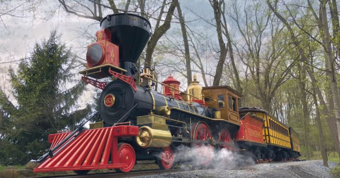 Red, Black and Shiny Brass steam locomotive, replica of Lincoln's funeral train steams through Pennsylvania woods