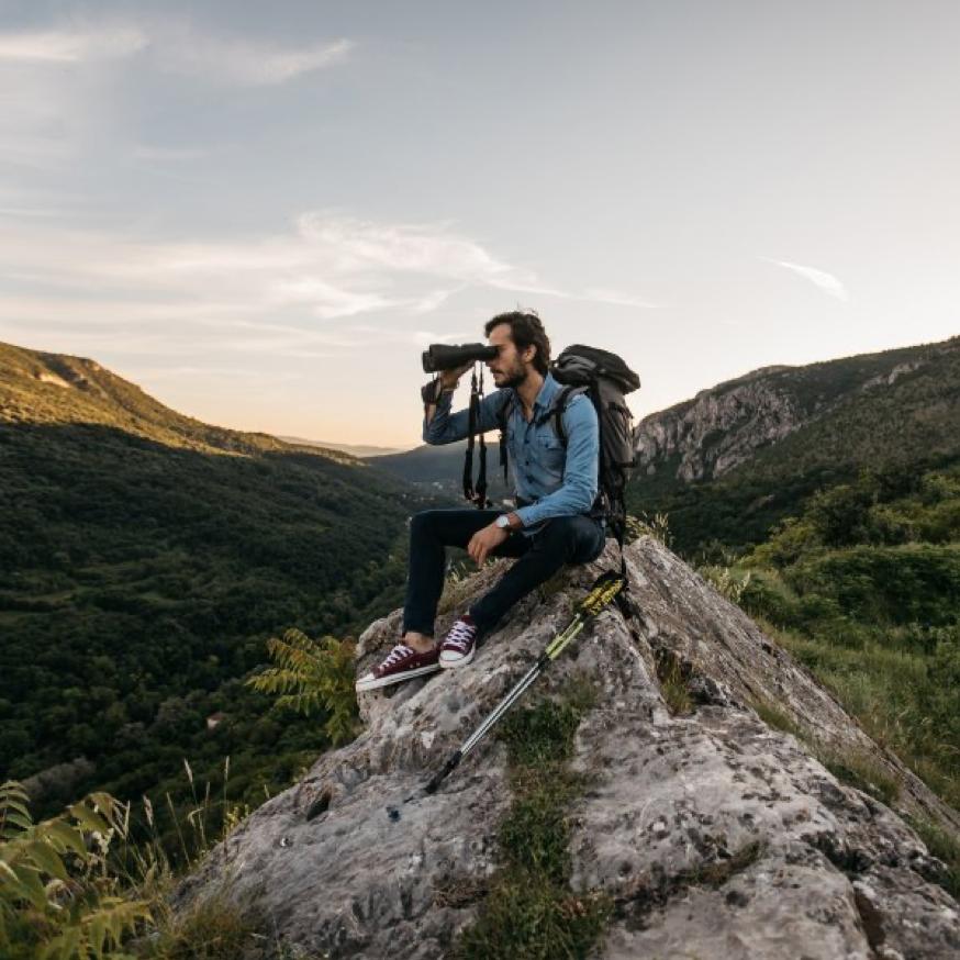 man on mountaintop with binoculars birdwatching