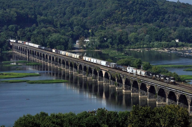 """A long, modern freiight train crosses the famed """"Rockvale Bridge"""" just west of Harrisburg, PA"""