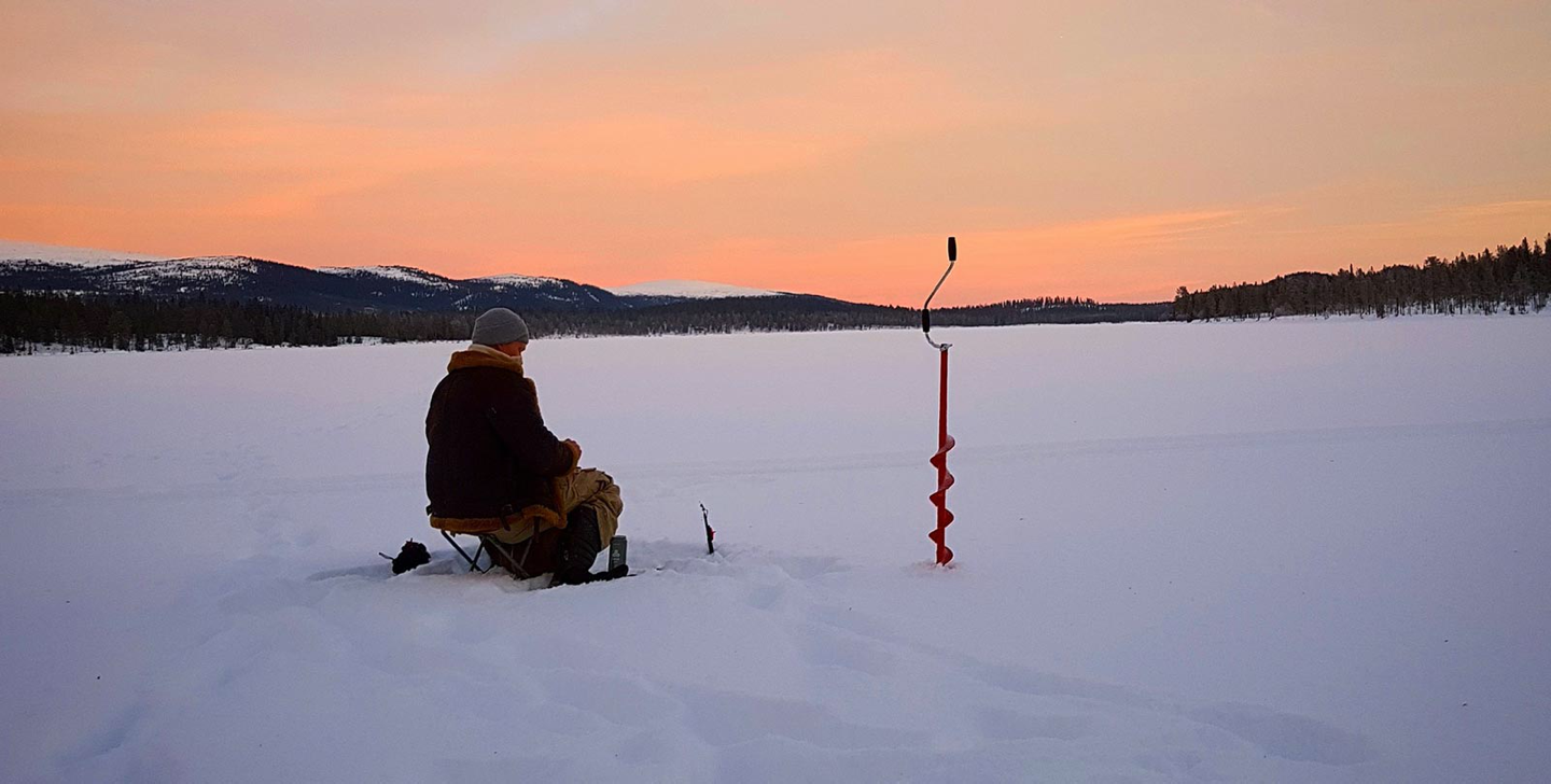 Ice fishing at sunset on frozen lake