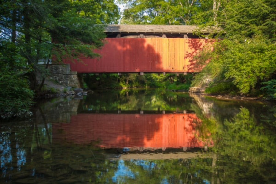 red covered bridge spanning a creek with bridge reflected in water