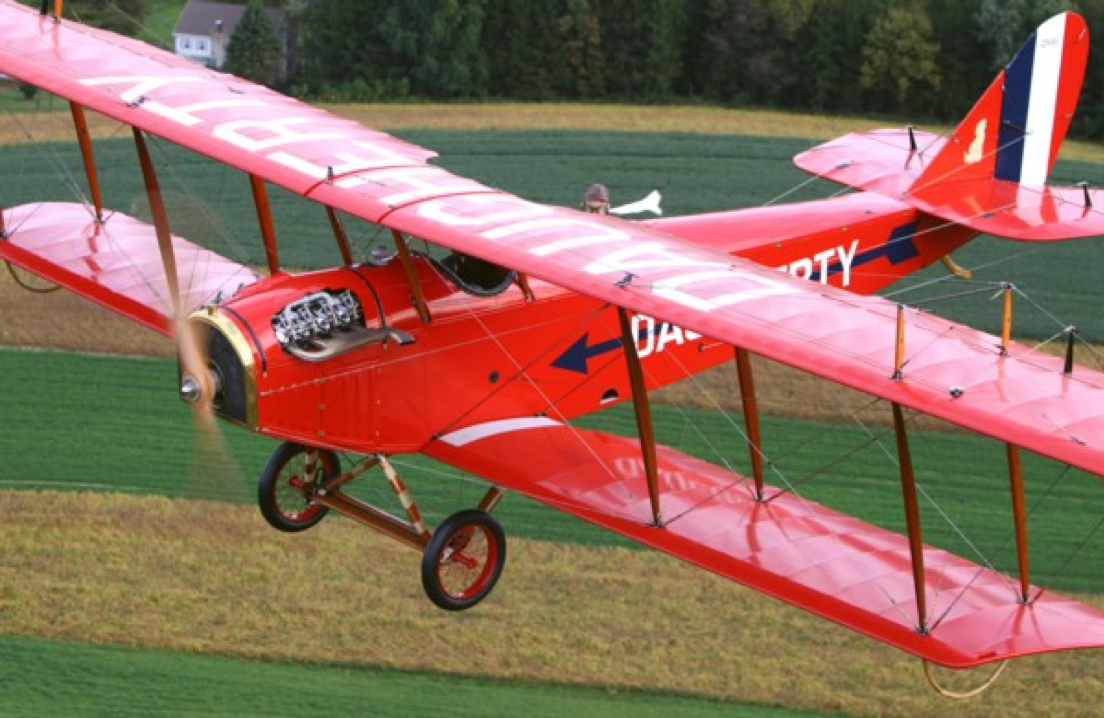 biplane flying low, colored orange-red