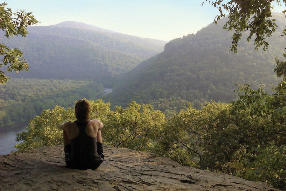 person sitting on a ledge overlooking mountains and river