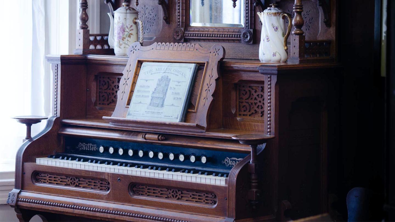 Antique pump organ with two antique serving pitchers