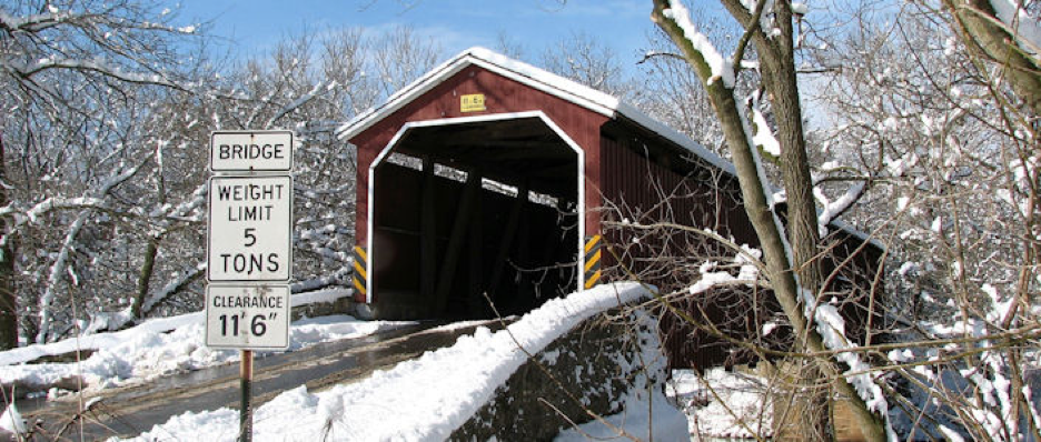 Covered bridge in forest scene shrouded in freshly fallen snow with bright blue sky