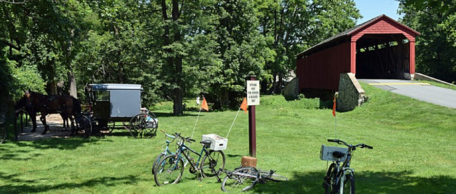 Red Covered bridge in background, Amish buggies and horses as well as bicycles parked at the river's bank