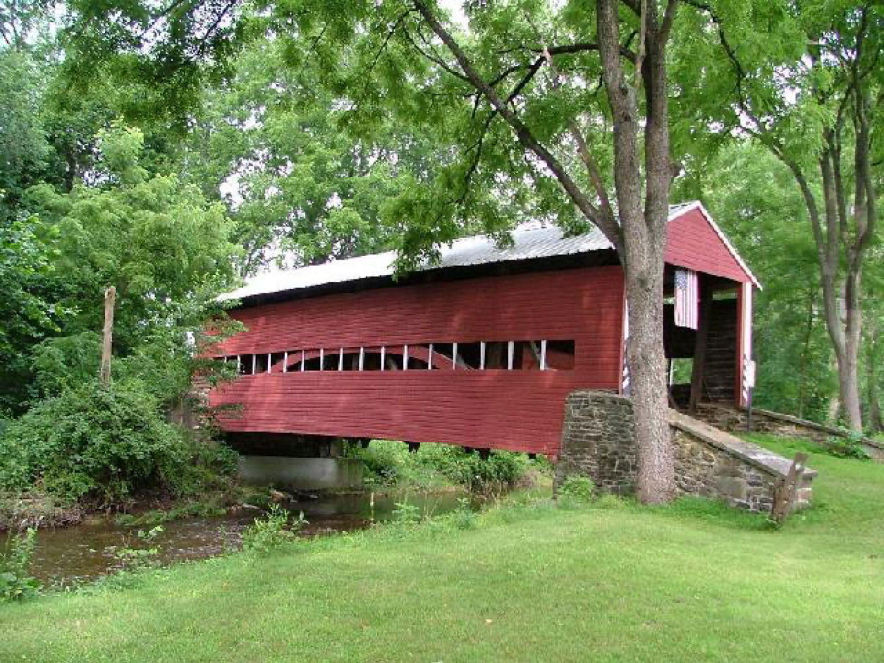 Long, red covered bridge with flag hanging from front. This bridge has a long line of windows along its sides.