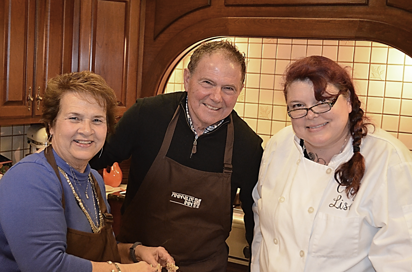 photo of chef with two student guests in kitchen