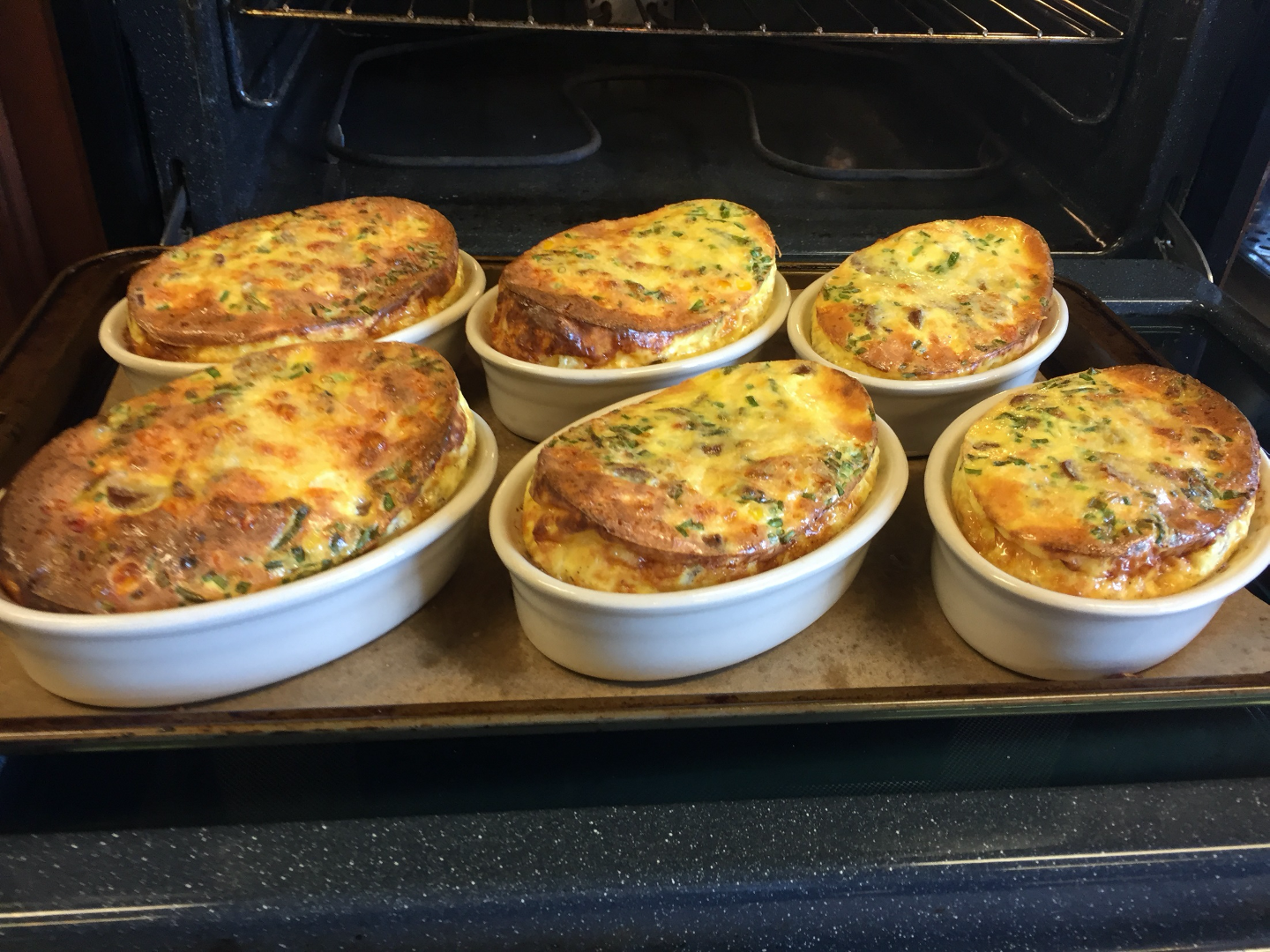 Quiche with chives coming out of oven
