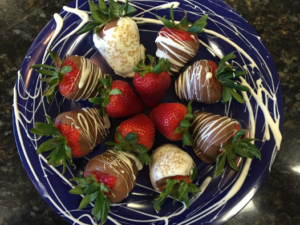platter of chocolate covered and decorated strawberries