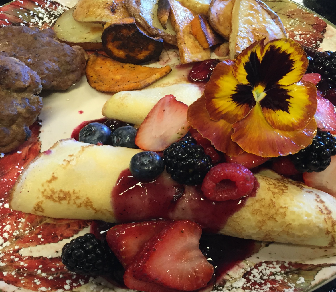 Breakfast at Annville Inn. Crepes with a warm berry sauce, home made sausage, oven roasted potato medly. Garnished by a unique colorful pansy.