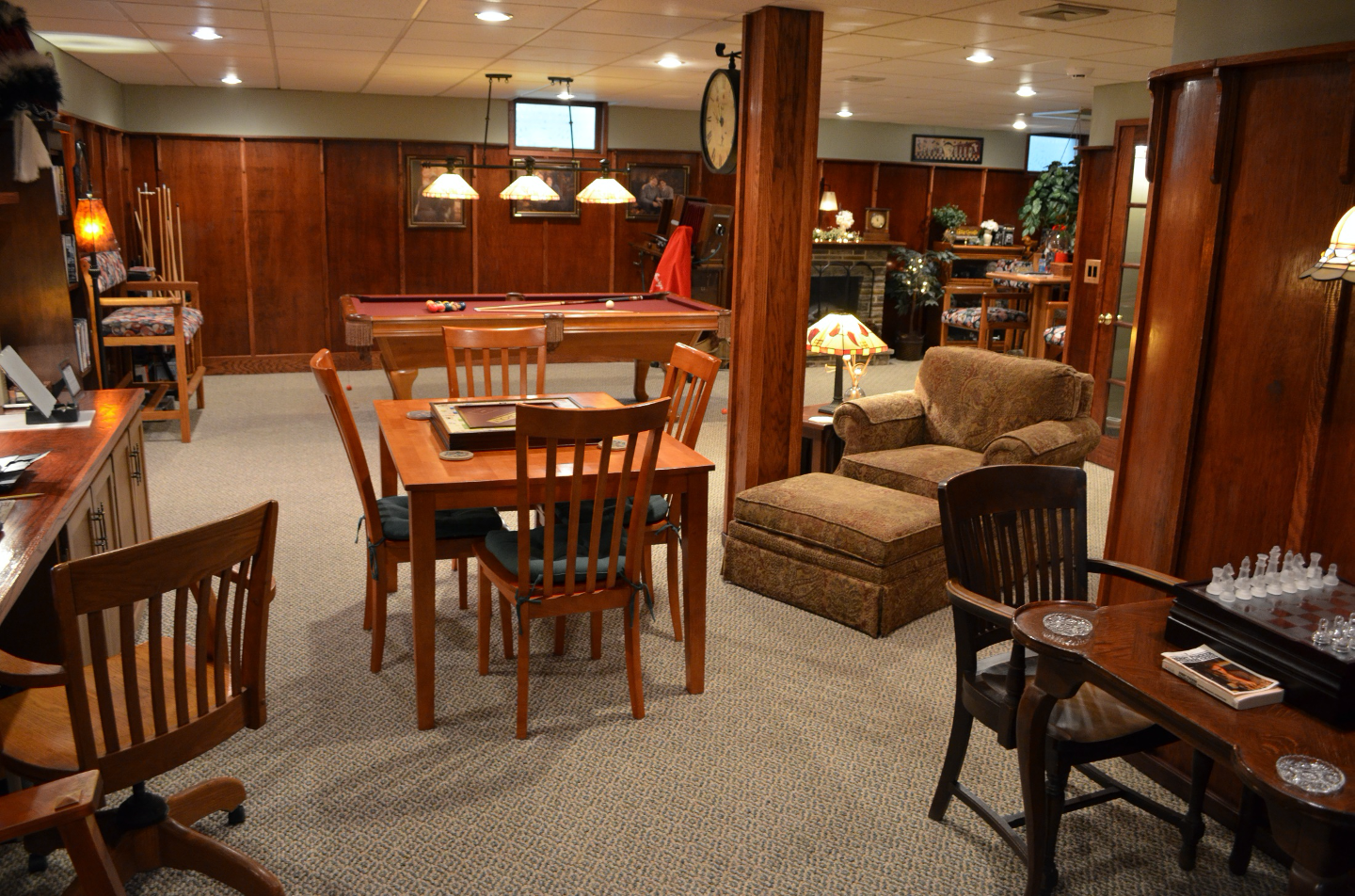 Vidw of Game Room showing three game tables, pool table, fire place, reading chair