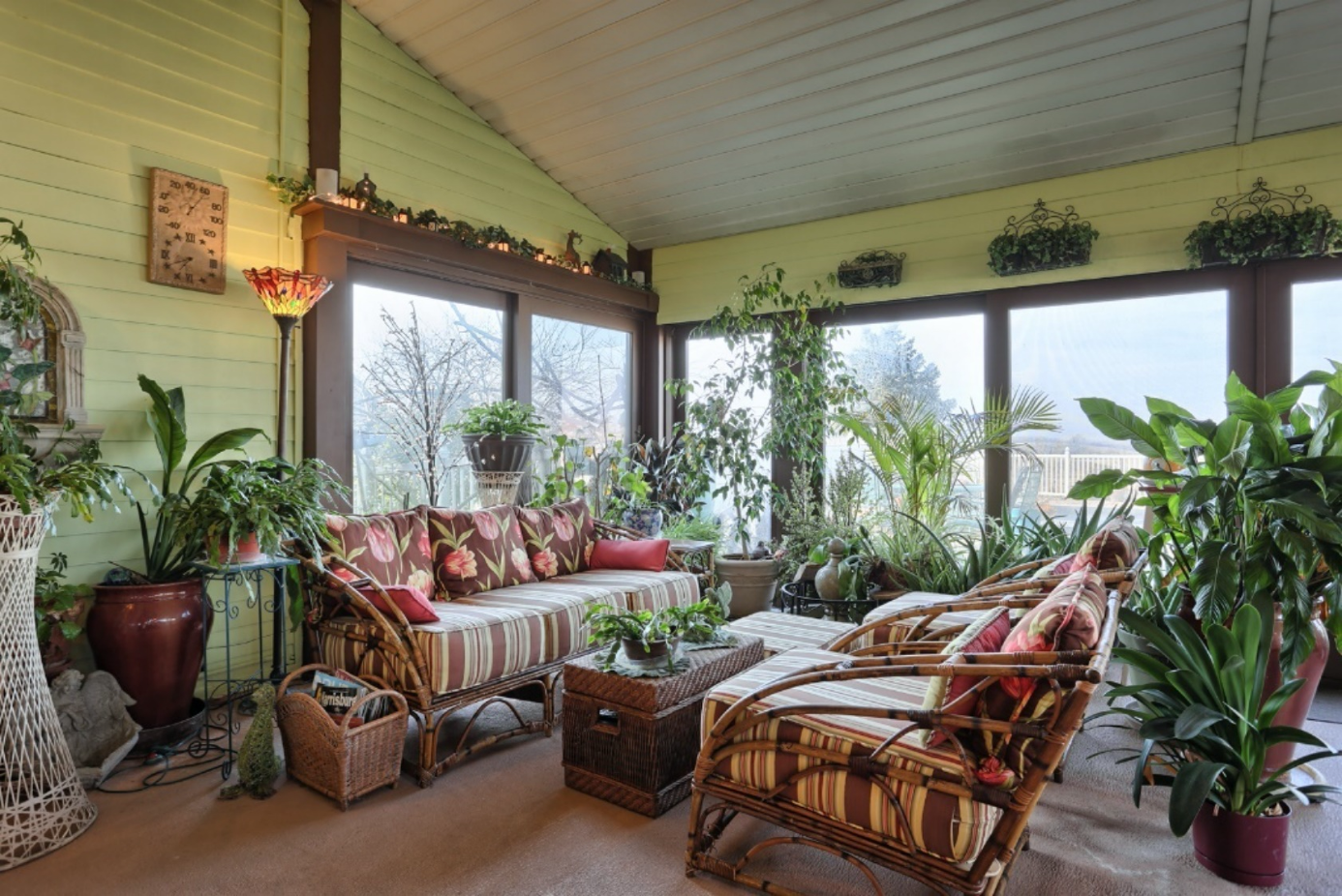 Seating in northwest corner of garden room, surrounded by glass walls and beautifully upholstered furniture and lots of potted plants.