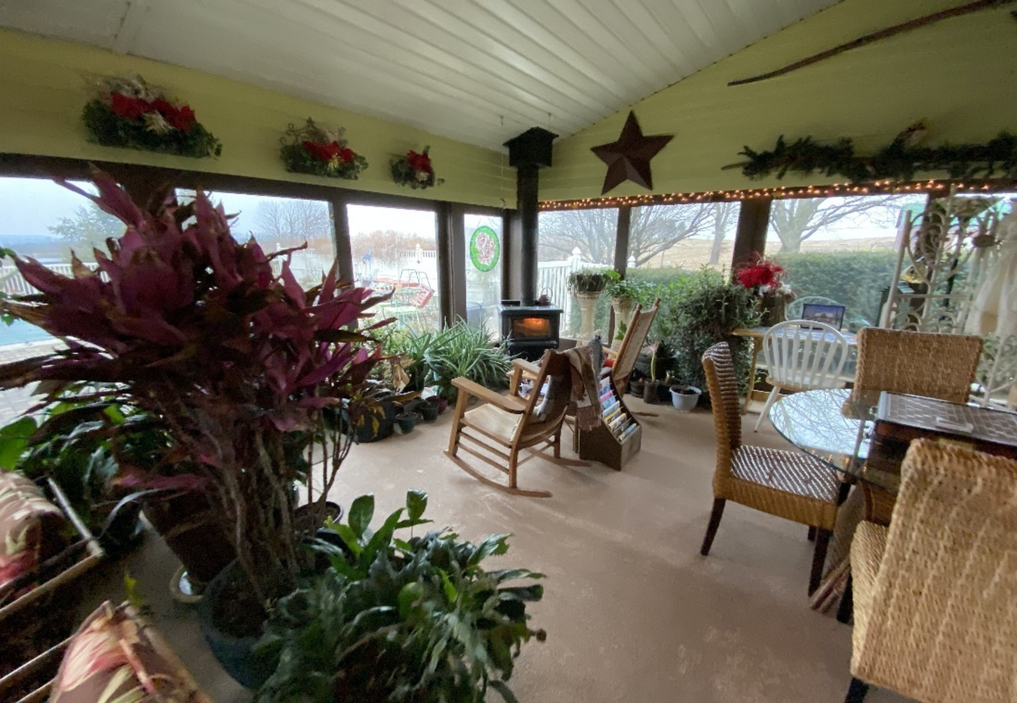 Garden Room with big windows on all sides, fire in fireplace.
