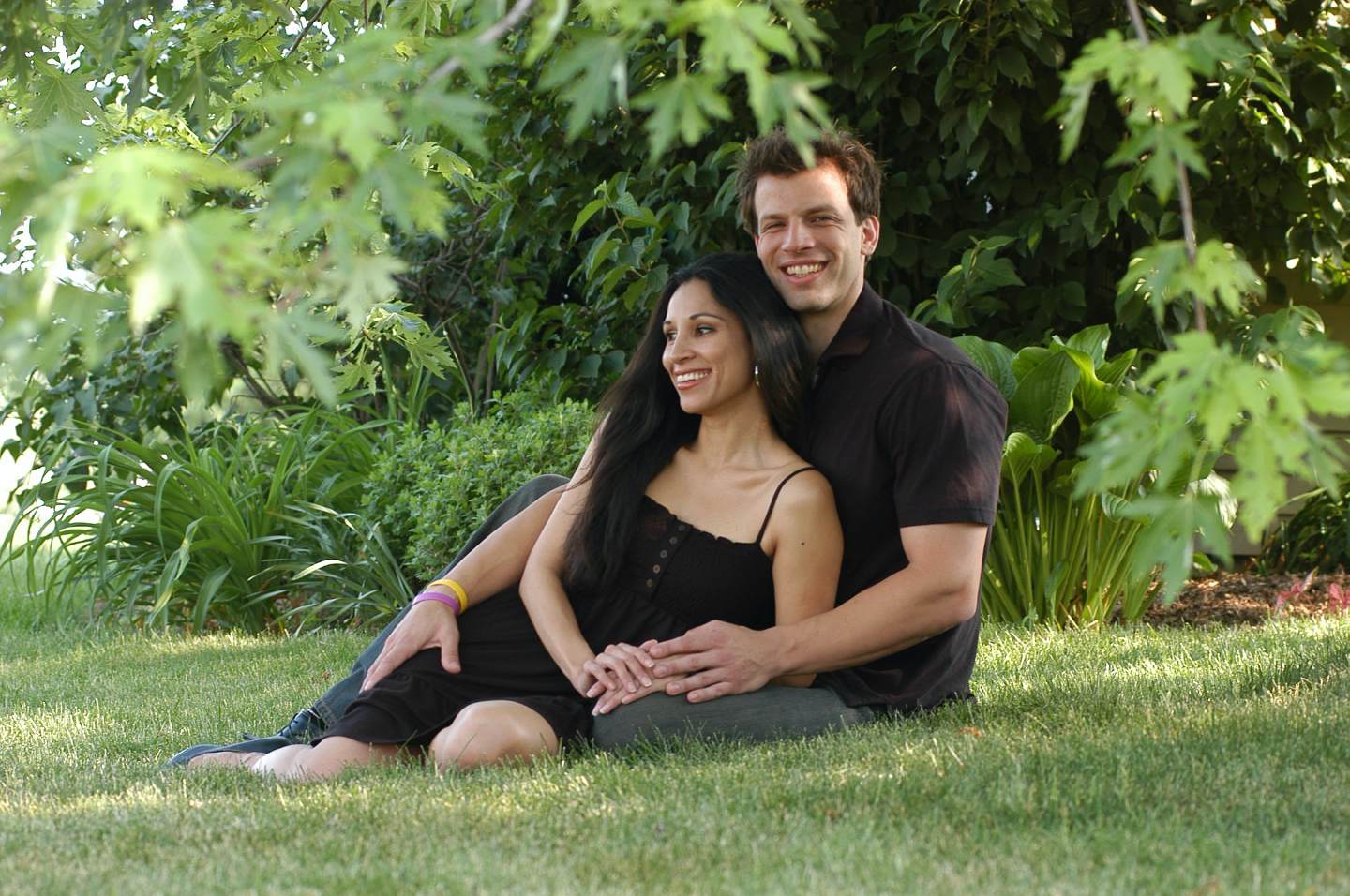 Portrait of couple outdoors: Handsome young man seated on ground with long haired young lady. Both smiling brightly.