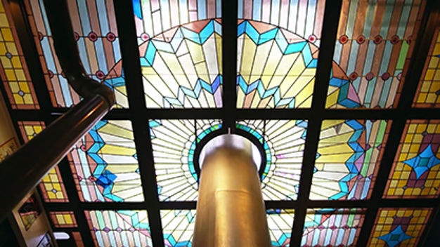 smokestack going up through a stained glass ceiling in a brewery