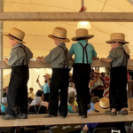 Four little Amish boys looking out over scene of Amish auction