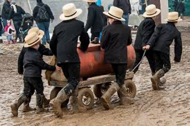 Six Amish boys move a tank on wheels through the mud