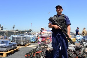 In this photo provided by the U.S. Coast Guard, a crewman from the Coast Guard Cutter Boutwell guards some of more than 28,000 pounds of cocaine, seized at sea and offloaded at Naval Base San Diego, Thursday, April 16, 2015. The vessel arrived with more than 14 tons of cocaine, part of what authorities described as a surge of seizures near Central and South America. (U.S. Coast Guard photo by Petty Officer 2nd Class Connie Terrell via AP)