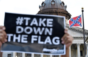 Hundreds of people protest against the Confederate flag (C) during a protest rally in Columbia, South, Carolina on June 20, 2015. The racially divisive Confederate battle flag flew at full-mast despite others flying  at half-staff in South Carolina after the killing of nine black people in an historic African-American church in Charleston on June 17. Dylann Roof, the 21-year-old white male suspected of carrying out the Emanuel African Episcopal Methodist Church bloodbath, was one of many southern Americans who identified with the 13-star saltire in red, white and blue.      AFP PHOTO/MLADEN ANTONOV        (Photo credit should read MLADEN ANTONOV/AFP/Getty Images)