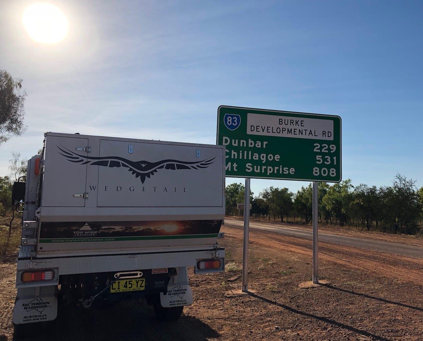 Truck camper beside road sign at start of BDR. Burke Developmental Road Conditions.
