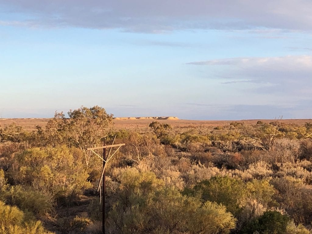 At Gregory Creek, taken from Old Ghan rail bridge. Overland Telegraph Line in foreground, flat-topped mesas in the distance. Salt Lakes and Water