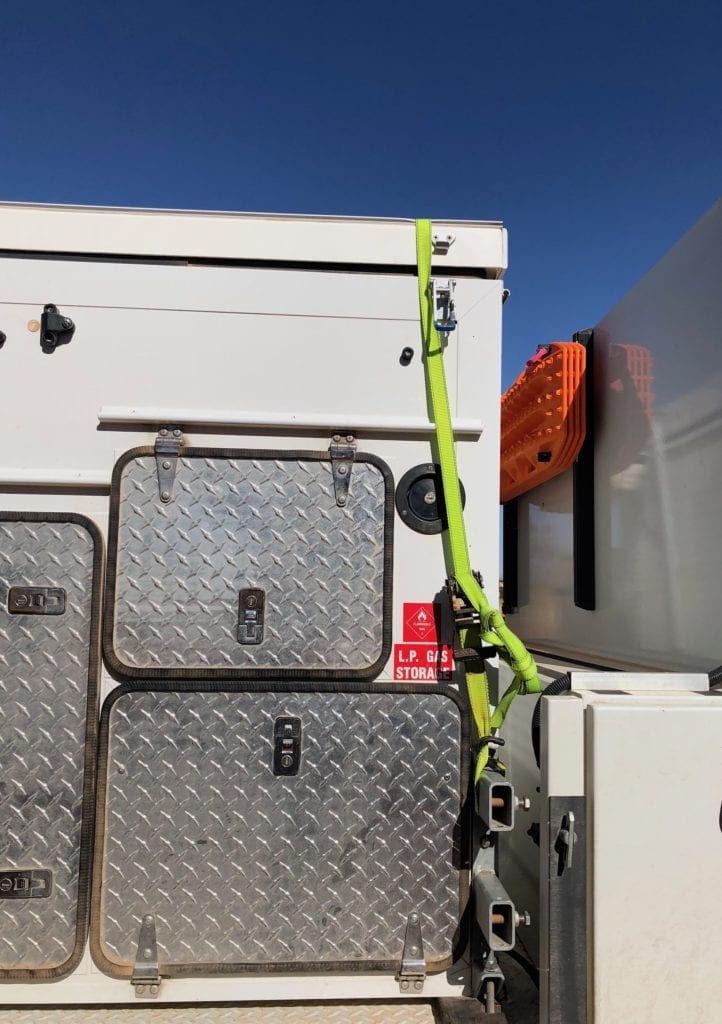 A ratchet strap temporarily holding our camper closed after a latch broke on the Finke track.