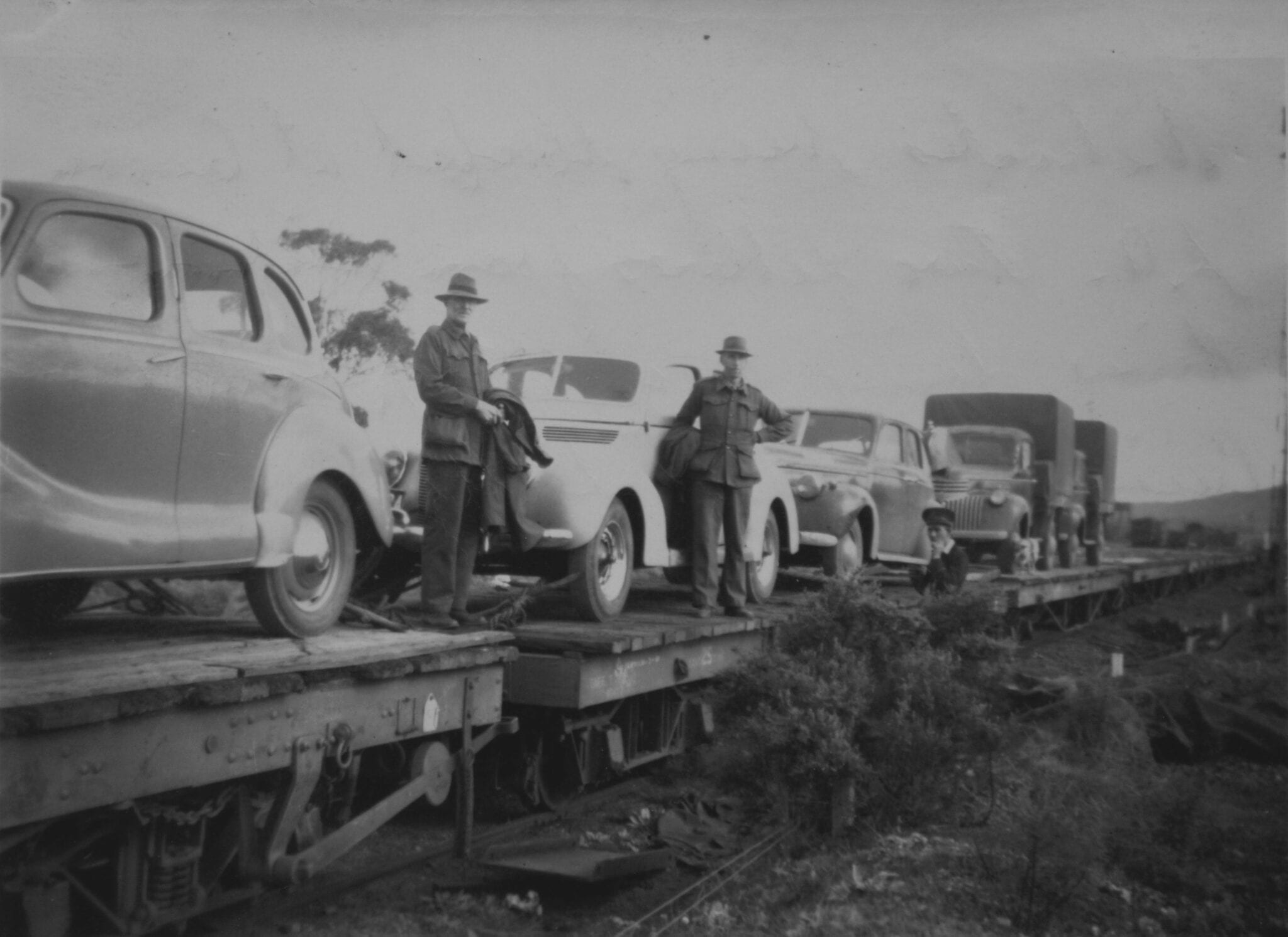 "Vehicles being loaded at Quorn S.A. Two fellows from Richmond River doing round trip via Darwin, Cairns etc also ""Sally"". Old Ghan."