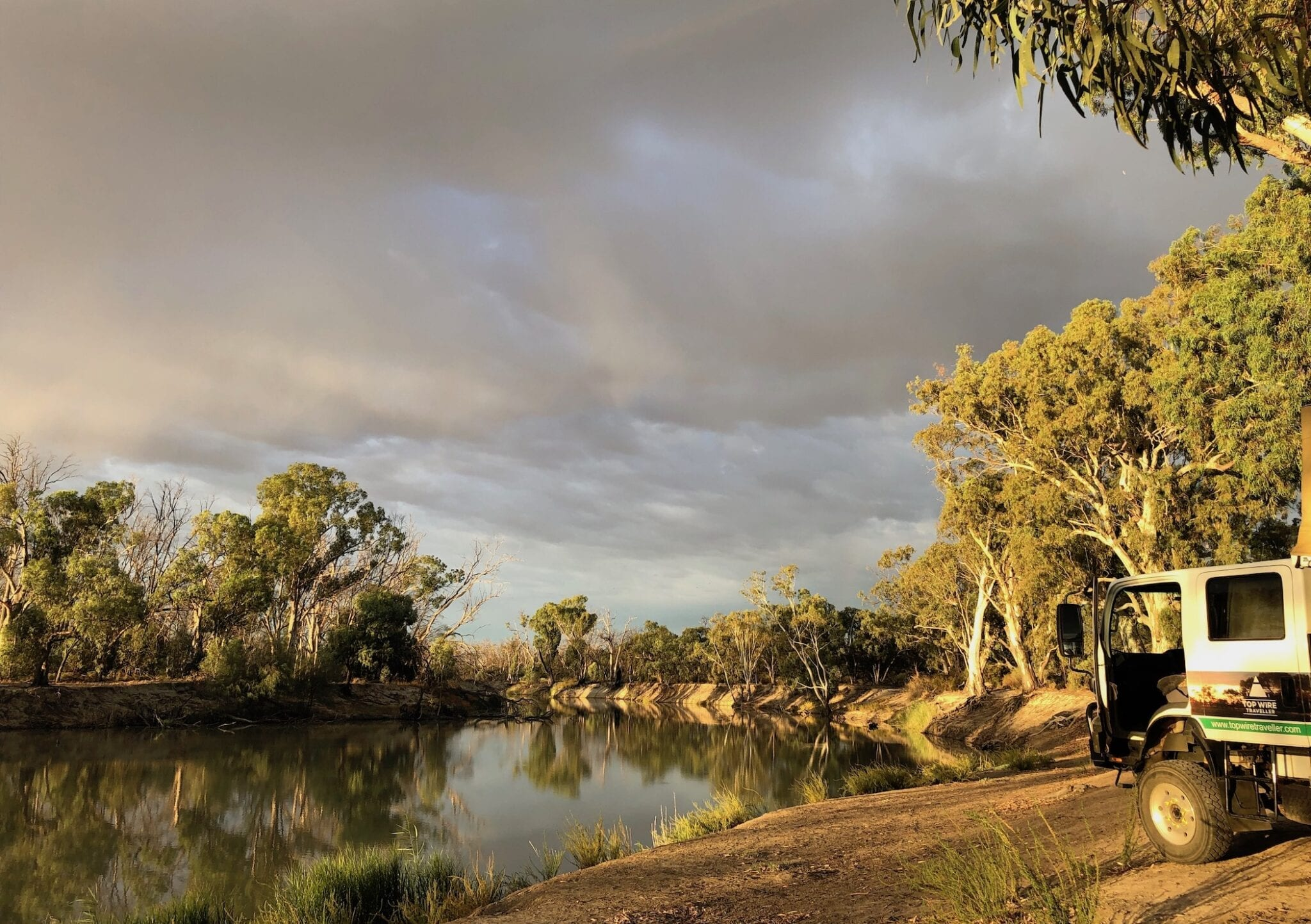 Camping On The Murray River, early morning light with dark clouds approaching.