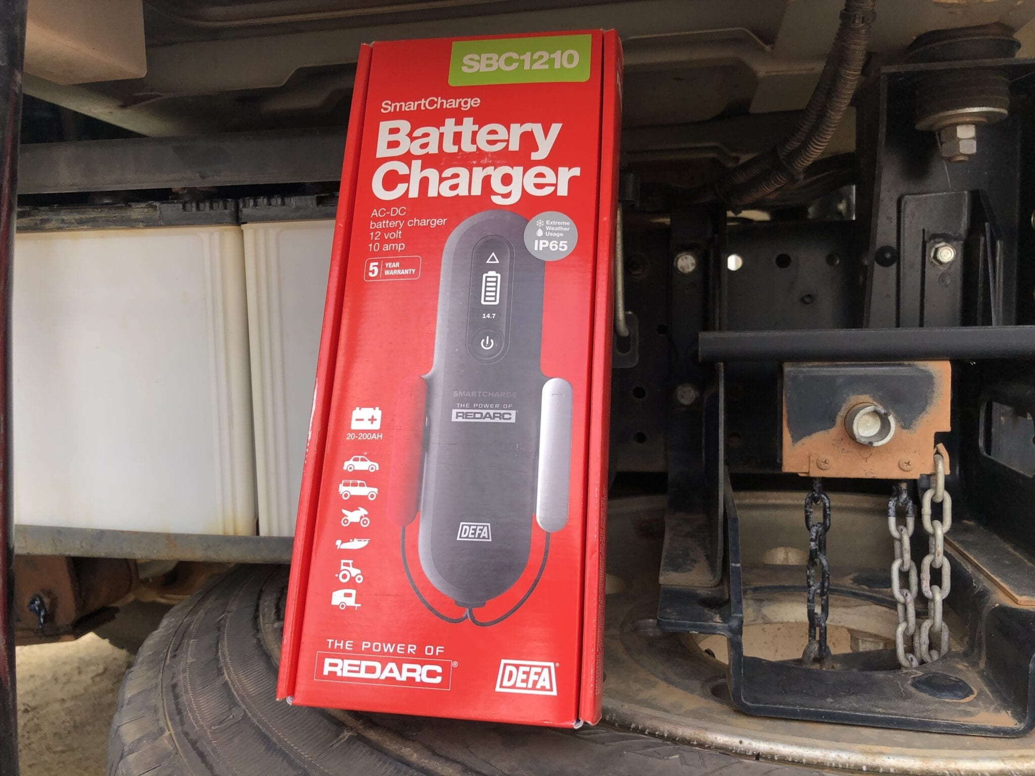 Our new REDARC battery charger pictured in front of our truck batteries.