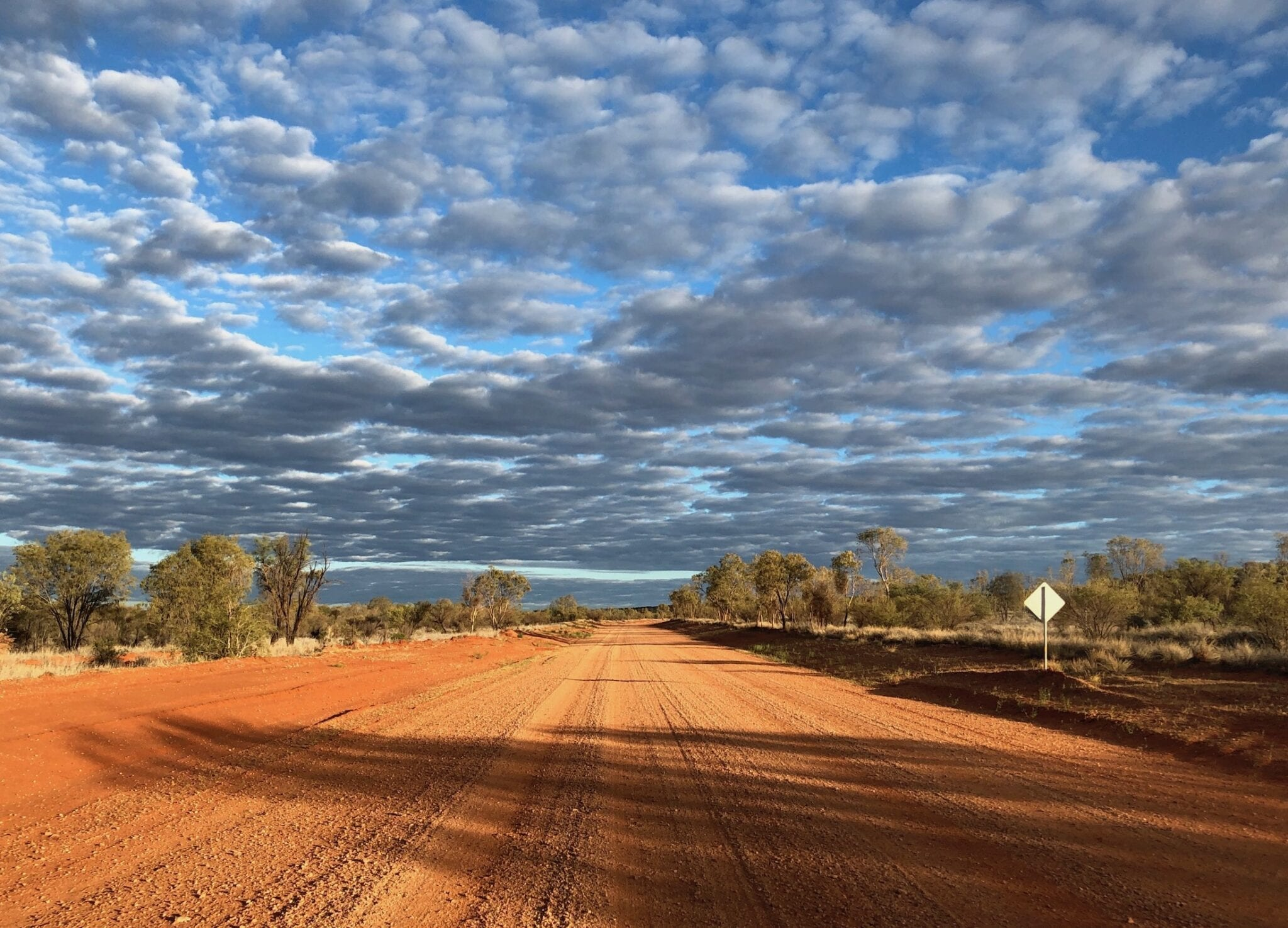 Dark clouds contrast sharply with the desert colours along the Sandover Highway, NT.
