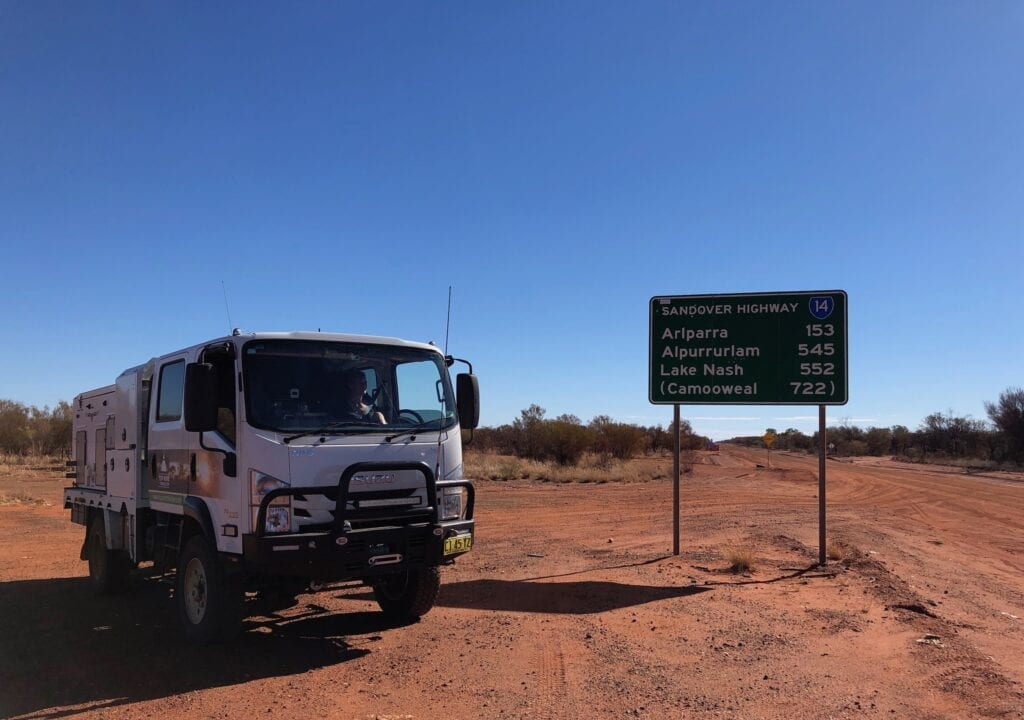 "Parked in front of the ""Sandover Highway"" sign at the eastern end."