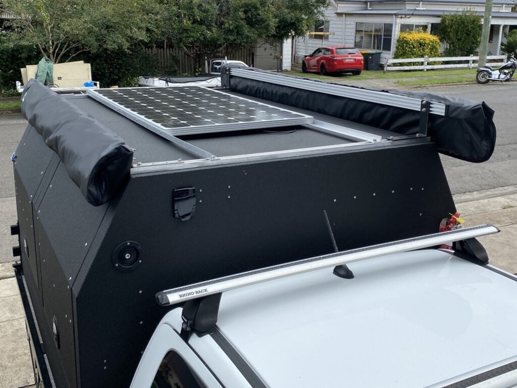Solar panel and two awnings mounted on a Wedgetail Hawk ute canopy camper.