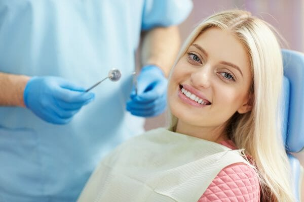 Woman Smiling While Getting Teeth Cleaning