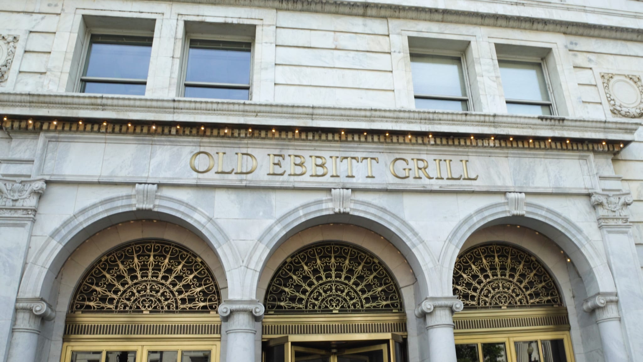 Old Ebbit Grill building entrance with gold lettering and doors.
