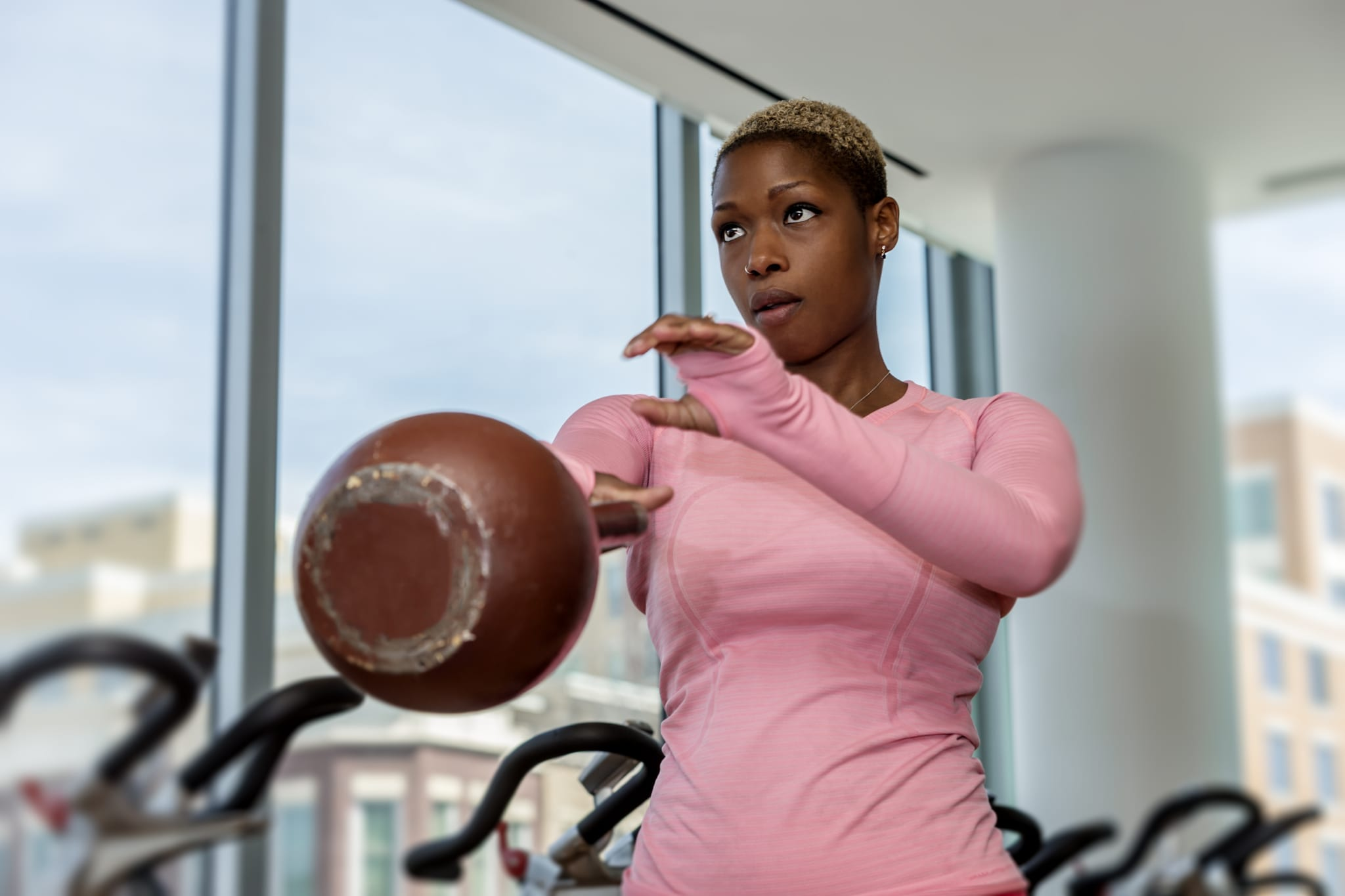 Close up of Sara lifting a kettle bell with her right arm.