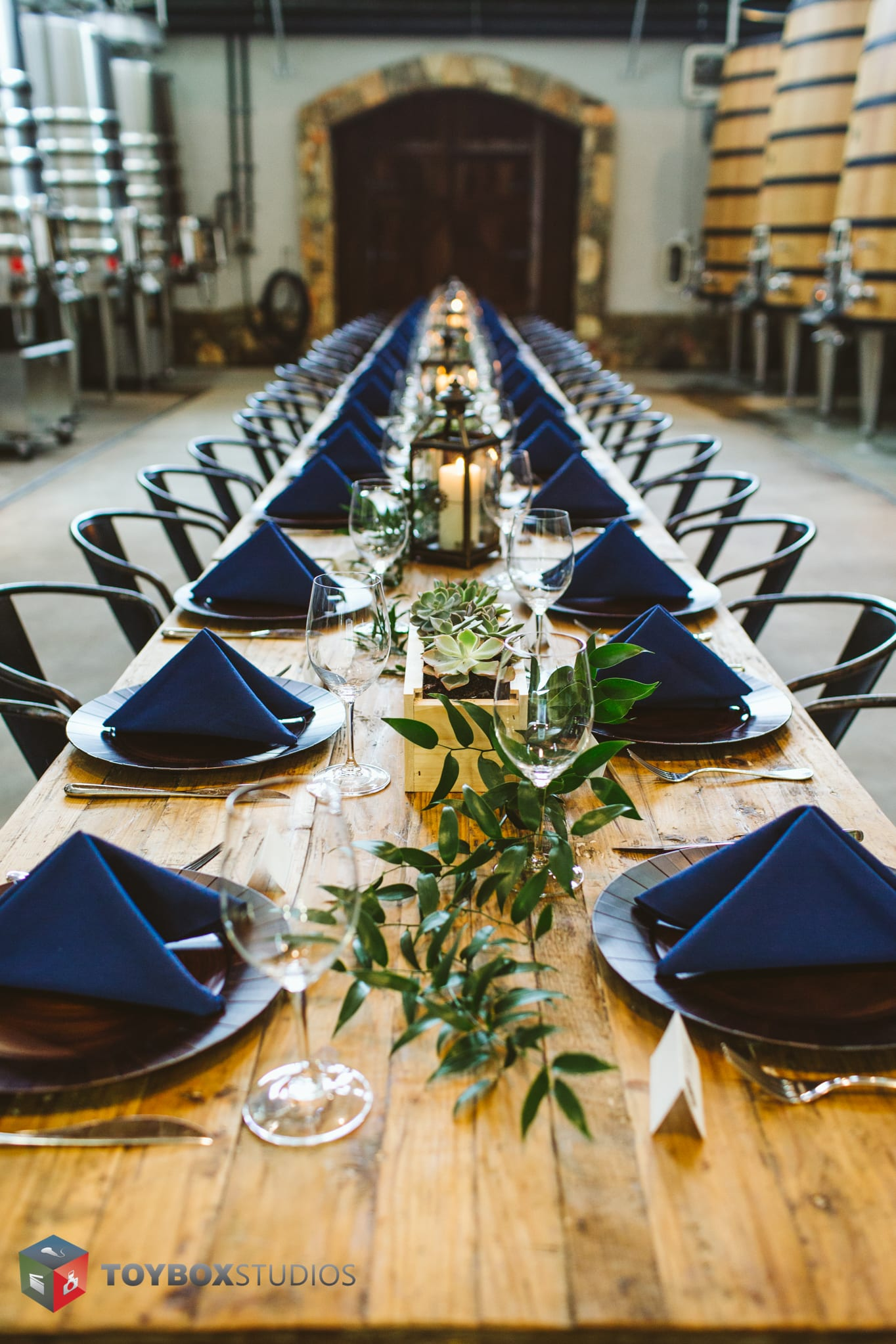 Stone Tower Winery Barrel Room Long Wooden Table Wedding Dinner Blue Napkins