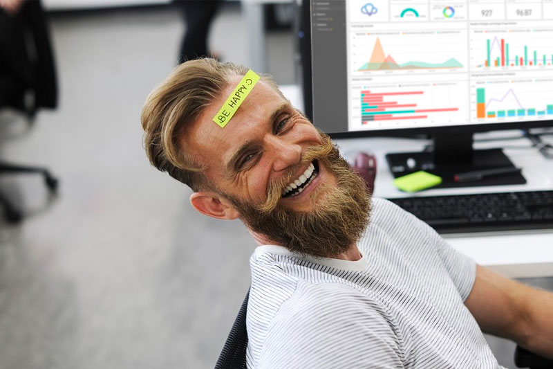 """Picture of a man smiling with a postit note on is head that says """"Be Happy"""""""
