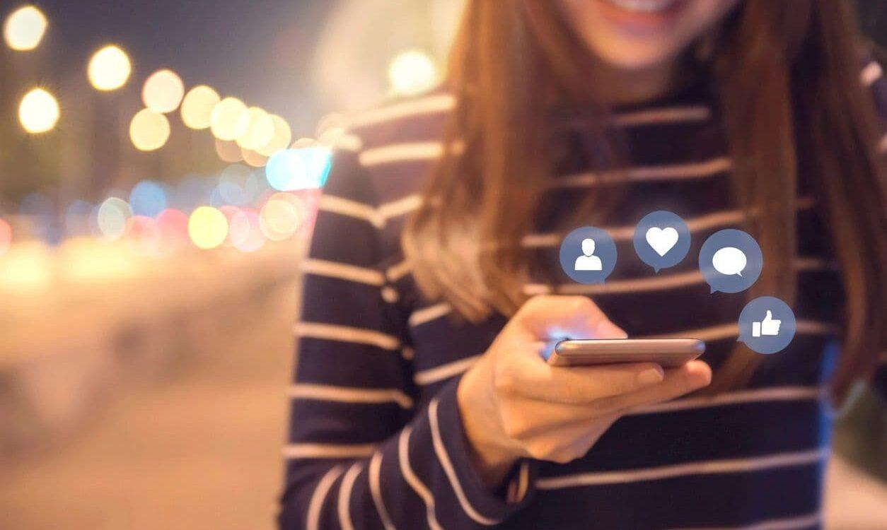 Girl looking at phone and smiling -Social Media Management