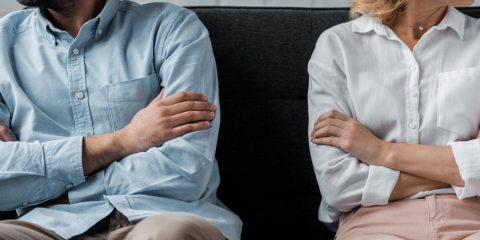 couple sitting on couch after quarrel