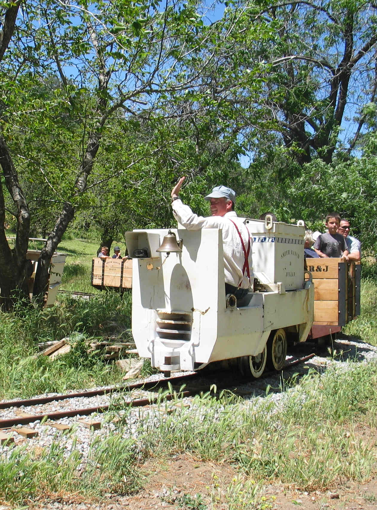 Author Gregory O. Smith driving a battery-powered Gold Mining Locomotive, pulling passengers in train cars, during his popular and successful living history adventure tour program.