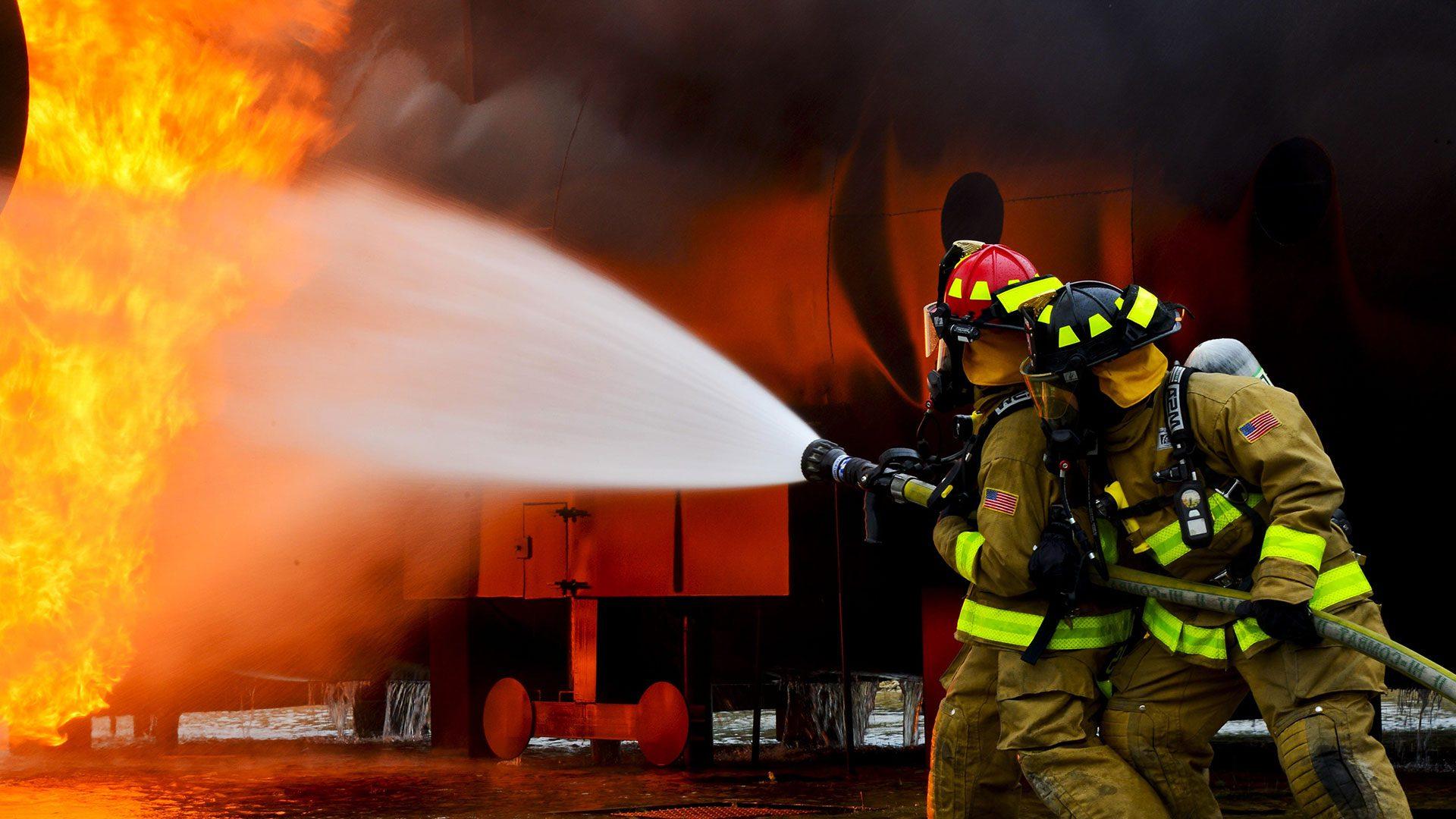 Firemen extinguishing a car fire.