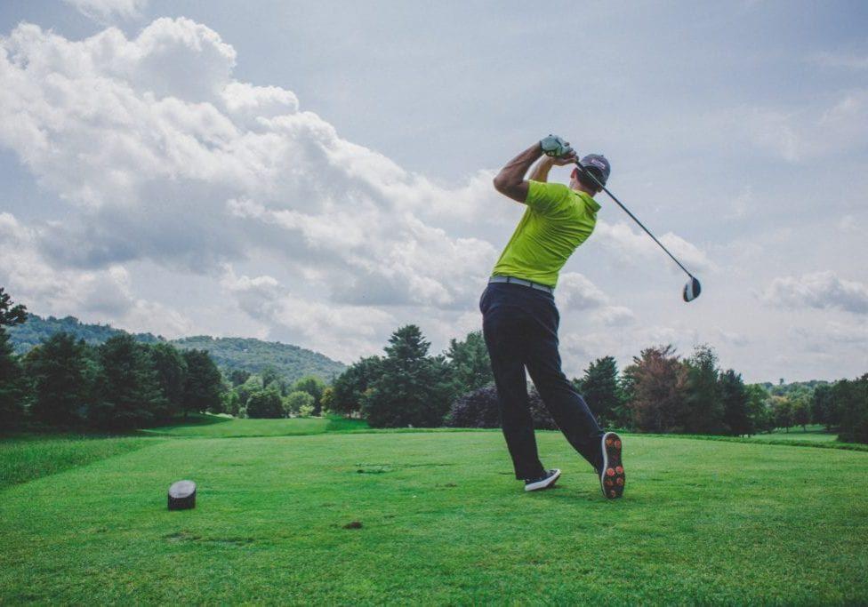 man swinging golf club on a beautiful day in Arizona
