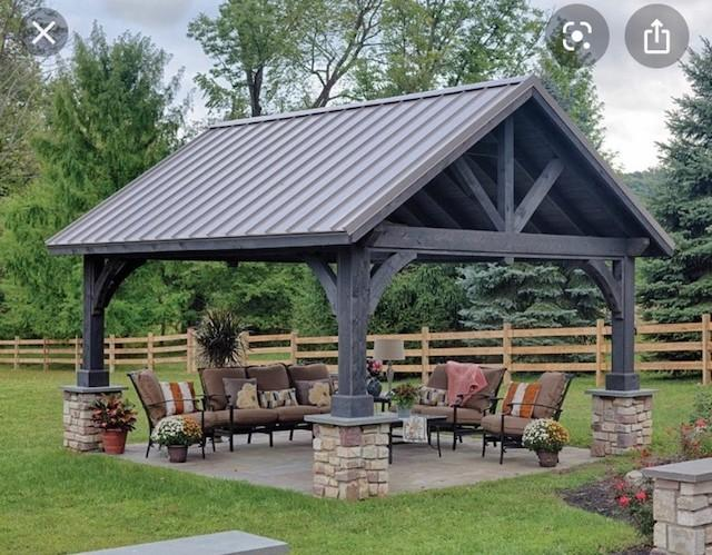 photo of outdoor covered pavilion wtih seating for 7 with table and lighting