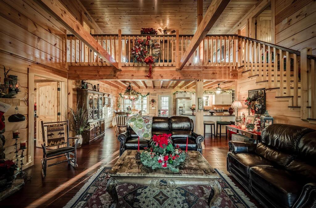 interior of log home with wood stairs, rails, ceilings, walls, floors and open rafters on both uppder and lower level ceilings.