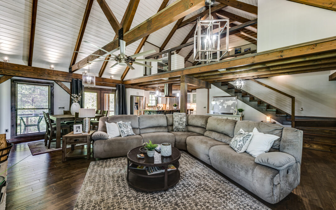 modern interior of log home with white painted wood walls and ceilings, open rafters and modern open staircase leading to loft