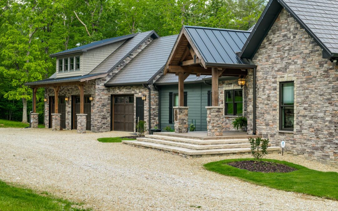photo of exterior of stone facade timberframe home with attached garage via a mudroom connection