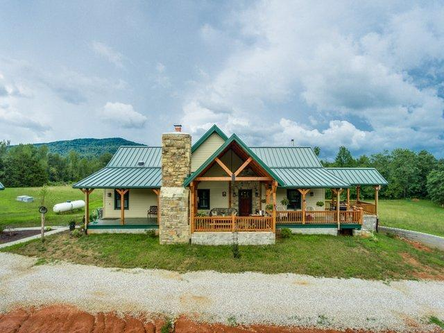 photo of log home with green metal roofing, wrap around porches, outside stone fireplace and a-frame porch