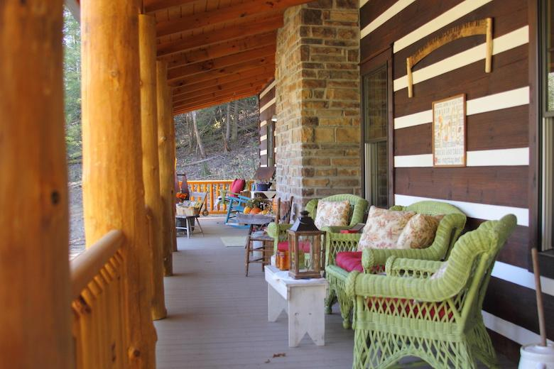 photo of chink log home with covered living space in outdoor wrap around porch system