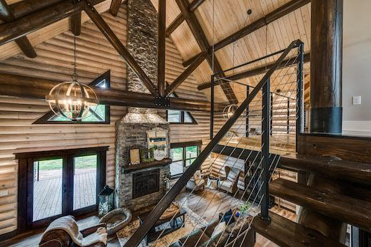 photo of great room from modern open staircase looking into living room with two story stone fireplace, exposed wood ceilings and walls and floors with wood framed rafters